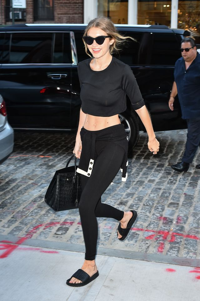 Gigi Hadid wears a black crop top, leggings, sweater, bag, and slides.