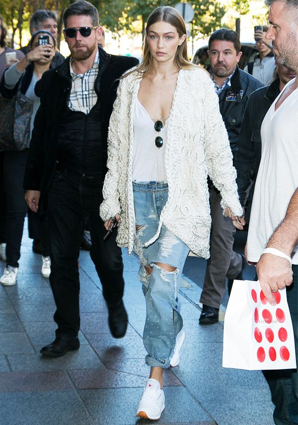 On Gigi Hadid: Jonathan Simkhai Braided Pearl Jacket ($8950); Ray-Ban Rb3547 Oval Flat Sunglasses ($150); Re/Done The Muscle Tee in Optic White ($78); Rag & Bone Dre Jeans in...