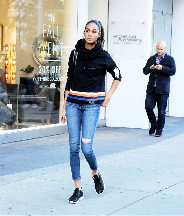 Joan Smalls wearing a P.E. Nation jumper, blue jeans and black sneakers in New York City.