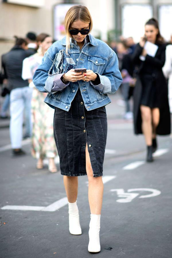 Pernille Teisbaek wears a denim jacket over a black denim skirt and white ankle boots.