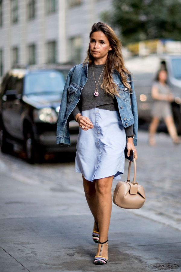 Miroslava Duma wears a shirt dress, grey sweater, and denim jacket.