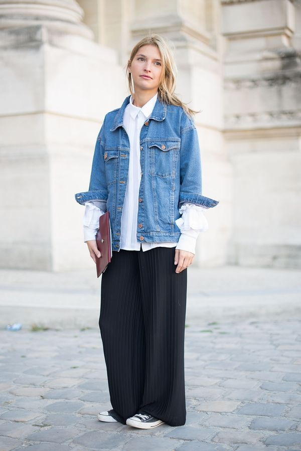 A street styler wears a white shirt, denim jacket, and black wide leg pants with Converse.