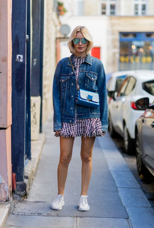 A street styler wears a denim jacket with a pink tweed mini dress and white sneakers.