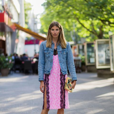 Veronika Heilbrunner wears a denim jacket, pink slip dress, and Converse sneakers.