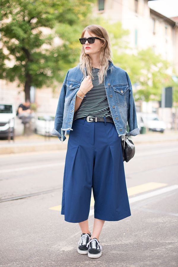 A street styler wears a blue denim jacket with a stripe top, navy culottes, and Vans sneakers.