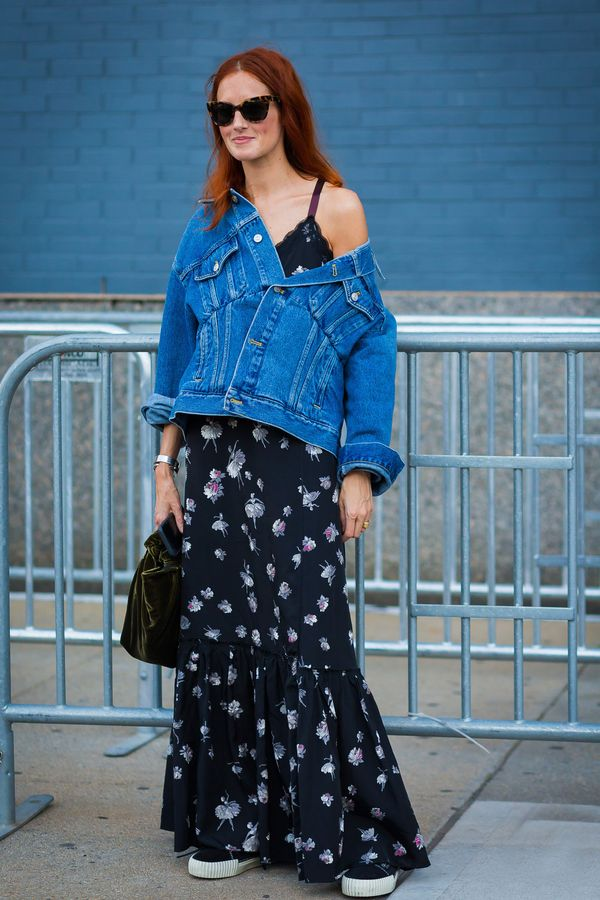 Taylor Tomasi Hill wears a floral maxi dress with a denim jacket and sneakers.