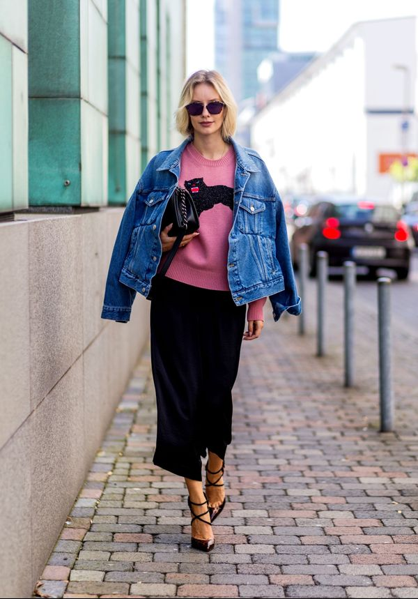 A street styler wears a blue denim jacket with a pink sweater and black culottes.