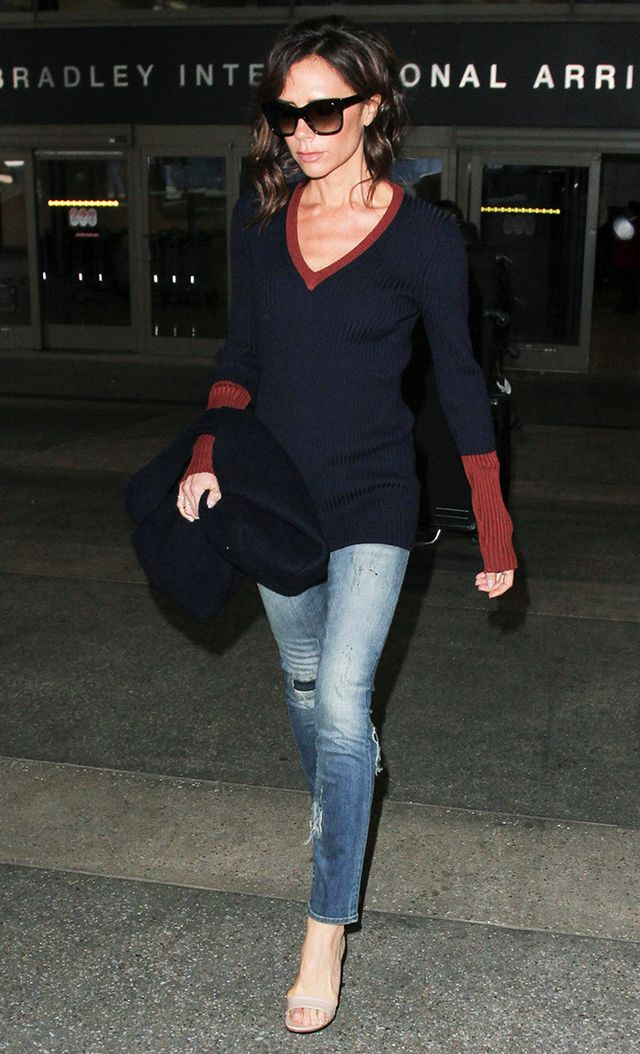 Victoria Beckham at LAX in sporty sweater, jeans, and heeled sandals