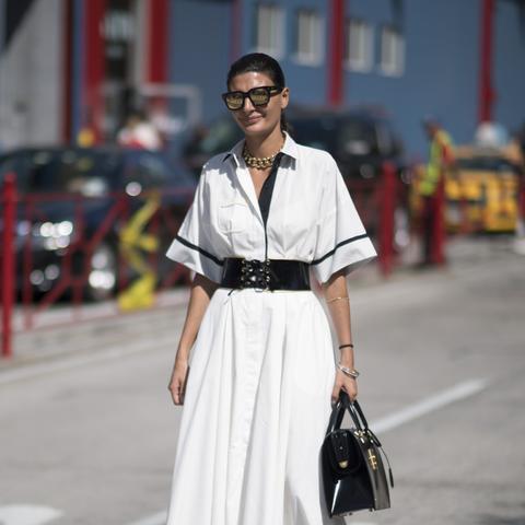 Giovanna Battaglia in a white dress, black belt, gold heels