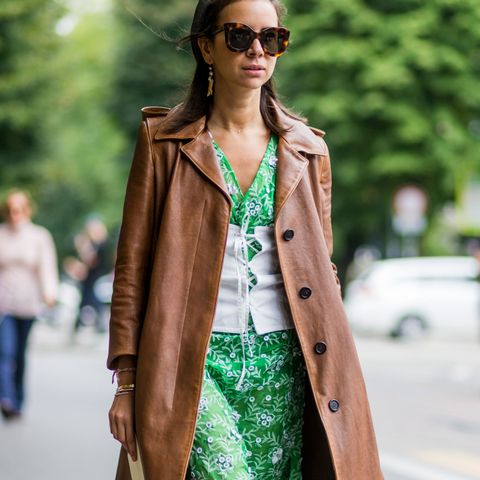 Natasha Goldenberg in a green dress, white corset belt and brown leather coat