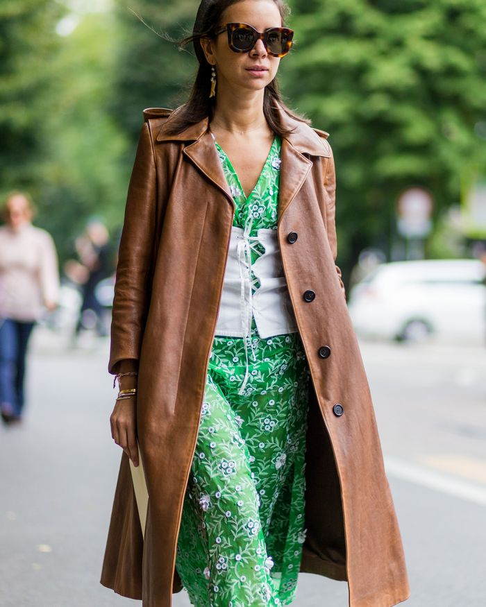 Natasha Goldenberg in a green dress, white corset belt and brown leather coat