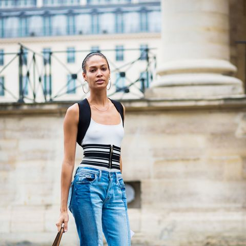 Joan Smalls in a white bodysuit, Frame Denim jeans, and corset belt.