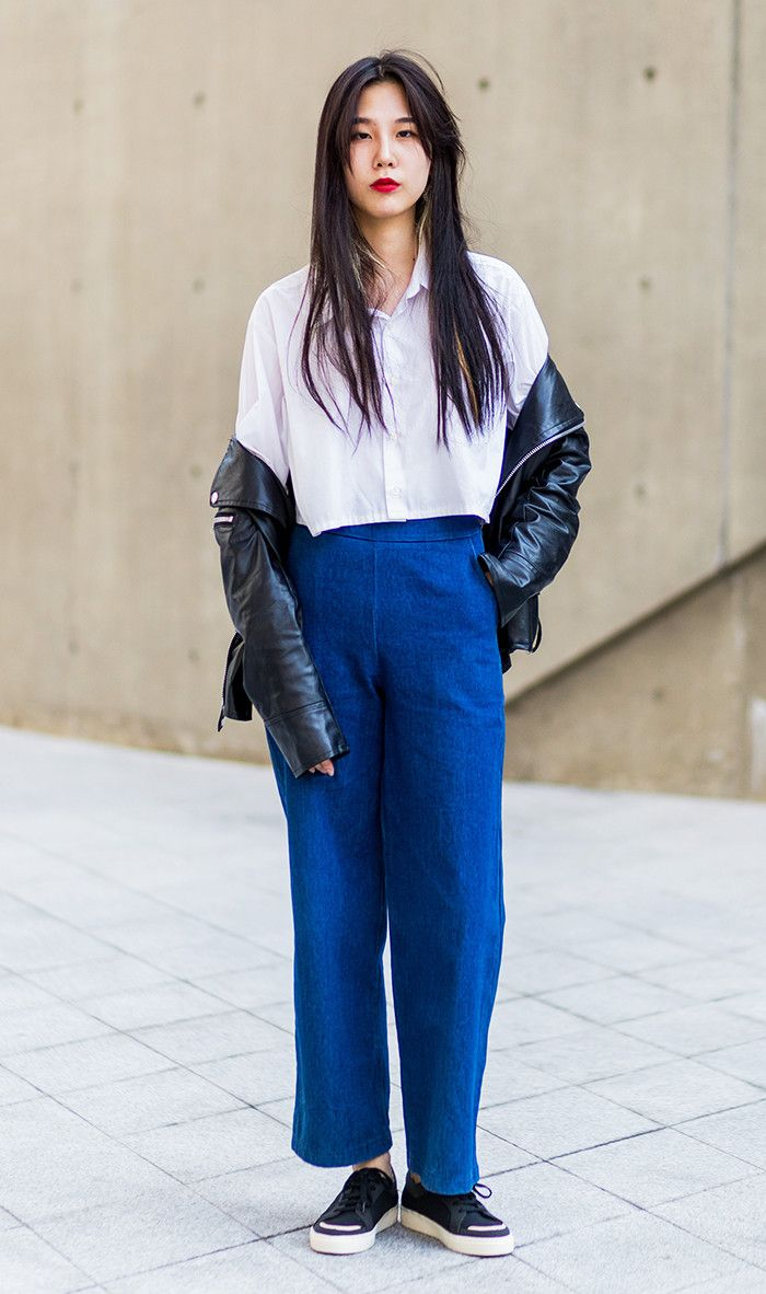 Woman wearing white button shirt, black leather jacket, blue denim jeans at HERA Seoul Fashion Week