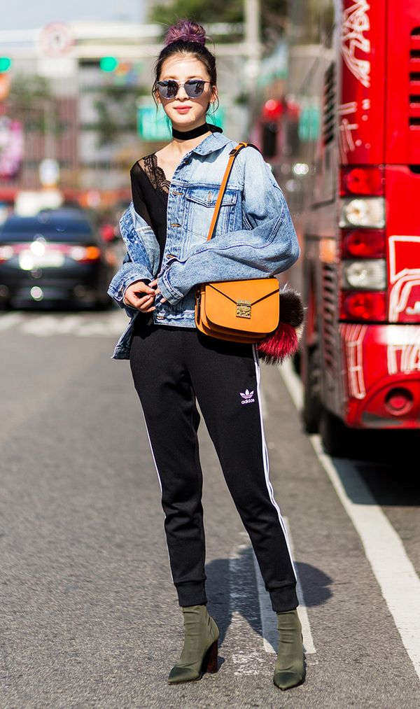 Irene Kim wearing a denim jacket, Adidas sweater pants, velvet boots and MCM bag at HERA Seoul Fashion Week