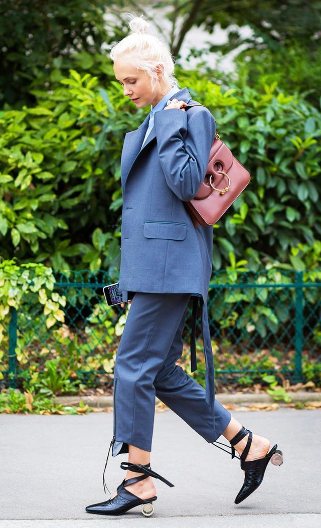 Olga Karput in blazer, trousers, and purse with circular hardware