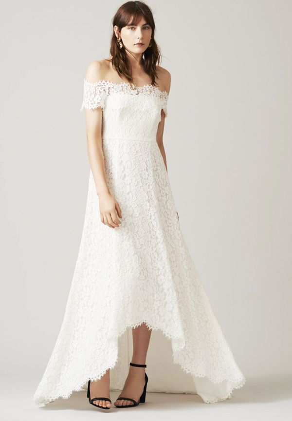 This is more of a classic wedding dress, but the off-the-shoulder top and the dip-hem make this super chic.