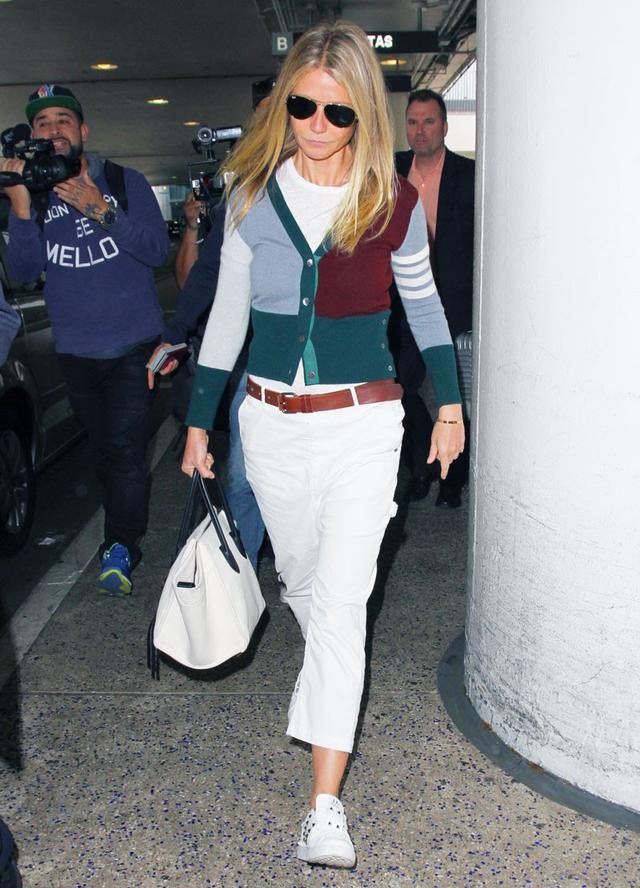 On Gwyneth Paltrow:Thom Browne Striped V-Neck Cardigan ($1790);Valentino Rockstud Leather Sneakers ($795); Céline Phantom Bag.