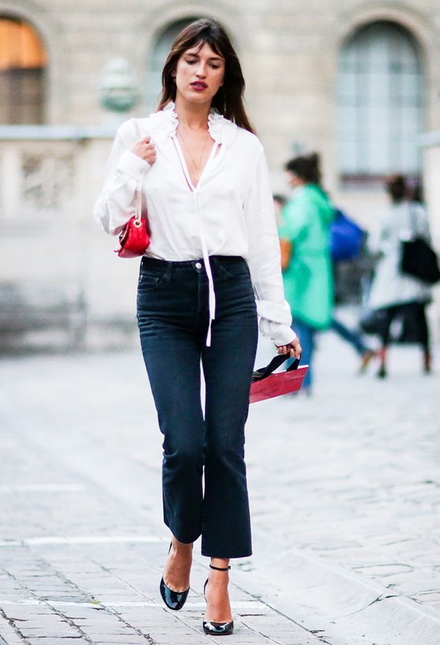 Jeanne Damas wears a white shirt, a red bag, and dark pants at Paris Fashion Week