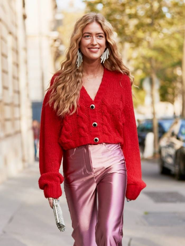 Showgoer wears drop sparkle earrings, red knit cardigan, pink metallic trousers.