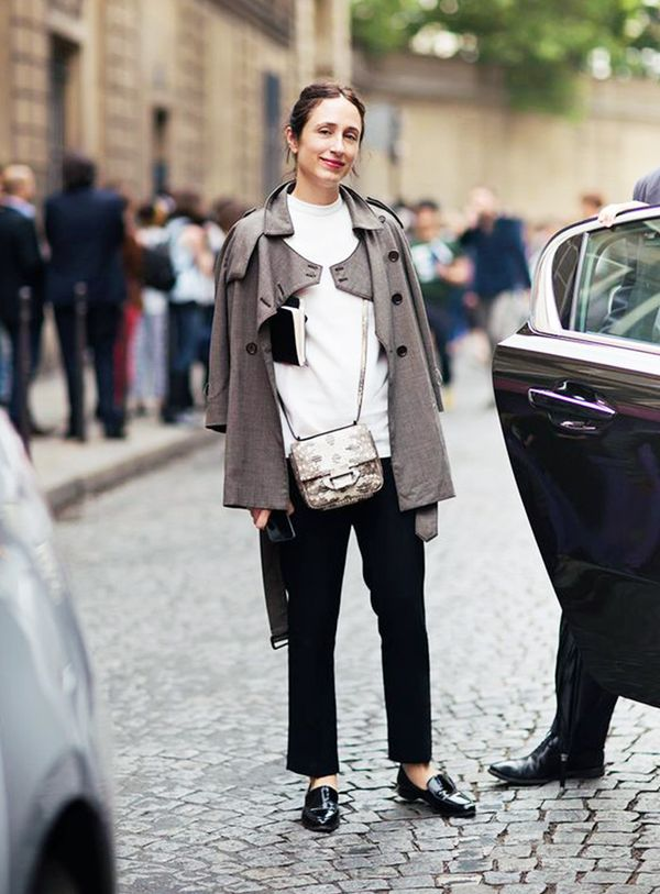Nicole Phelps in black pants, patent loafers, cape jacket, and crossbody bag.
