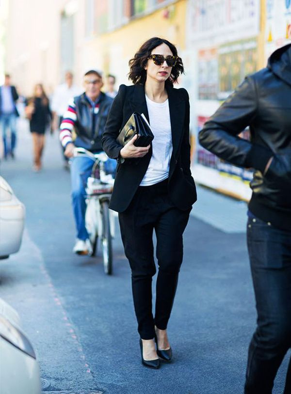 Nicole Phelps in blazer, black trouser, pointed heels, and tortoise sunglasses