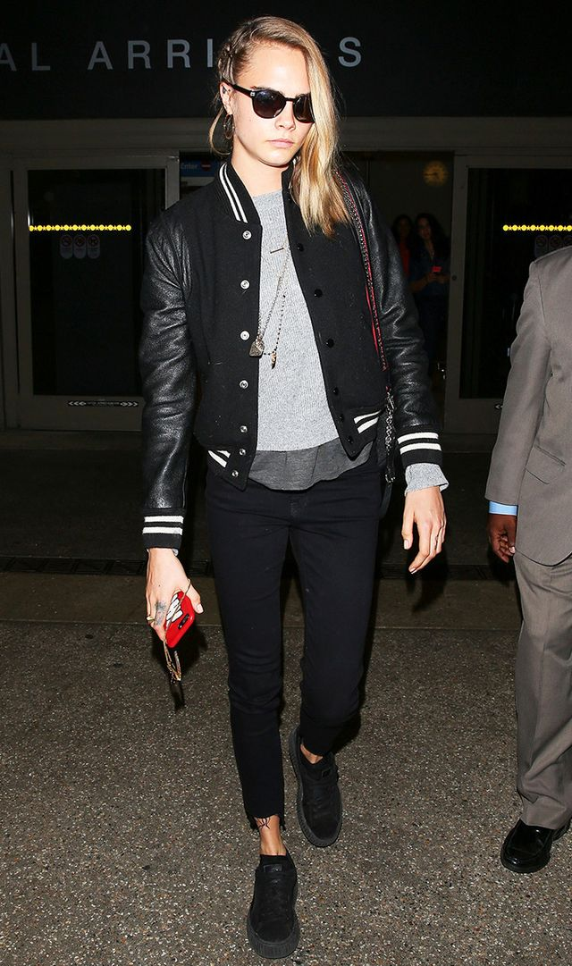 Cara Delevingne arrives at LAX in a black bomber jacket with braids