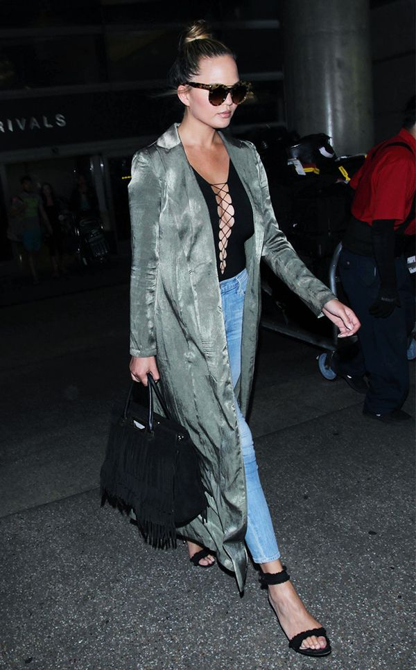 On Chrissy Teigen: Alexander McQueen Piercing Bar Sunglasses ($430); Naked Wardrobe Uptown Duster Coat ($24); T by Alexander Wang Lace Up Bodysuit ($160); Frame Le High Skinny in Waterford ($165);...