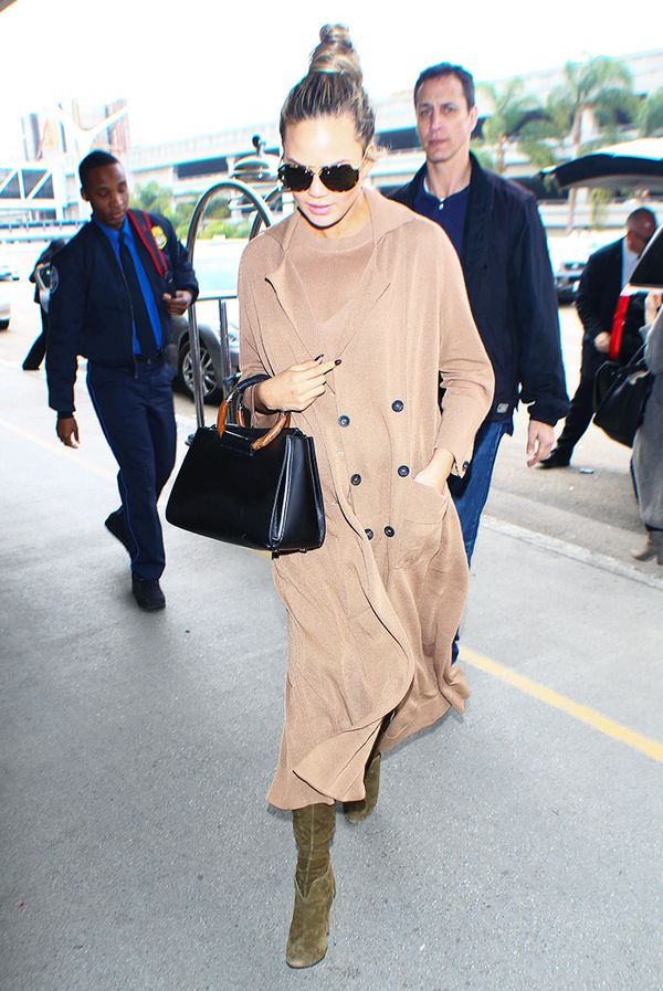 On Chrissy Teigen: Soyer Summer Trench Coat in Nutmeg ($724) and Sleeveless Tunic in Nutmeg ($158); The Row Round Handle Tote Bag (sold out).