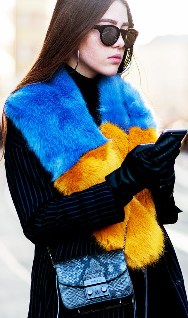 Antonia Voicu wearing a navy white stripped wool coat, leather gloves, a dark black Furla bag, a yellow blue fake fur scarf, sunglasses in Berlin, Germany.