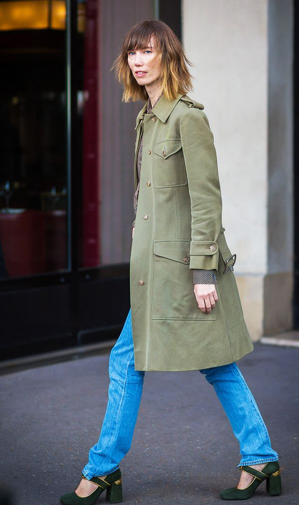 An army green military coat looks especially chic with a pair of blue jeans.