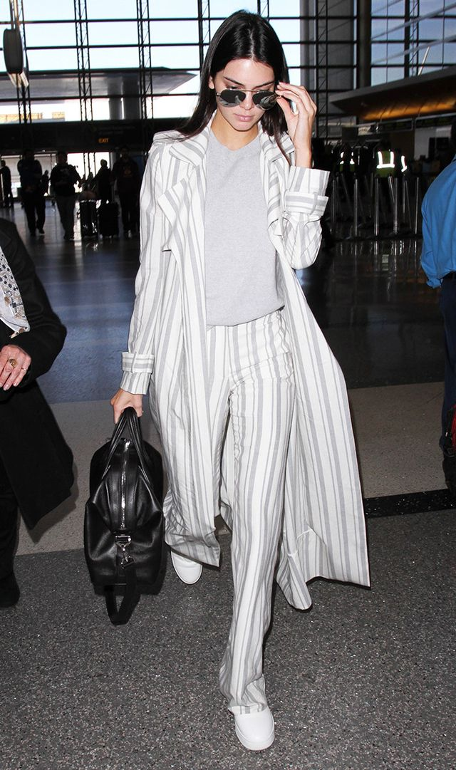 Kendall Jenner at LAX in white-and-gray trousers and duster, and gray sweater
