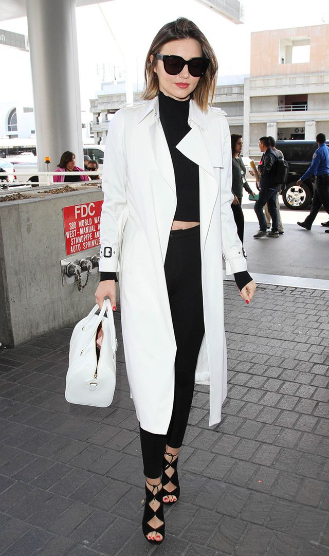 Miranda Kerr at LAX in cropped black sweater, black pumps, and white trench
