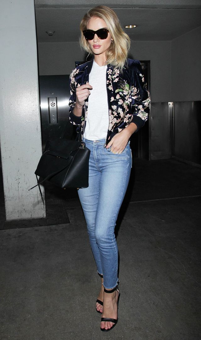 Rosie Huntington-Whiteley at LAX in jeans, white t-shirt, and floral bomber jacket