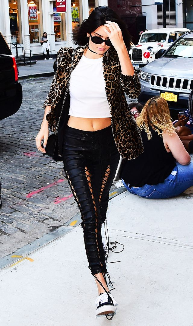 Kendall Jenner in New York City wearing front lace-up leather pants with cropped tee, leopard jacket, and sneakers