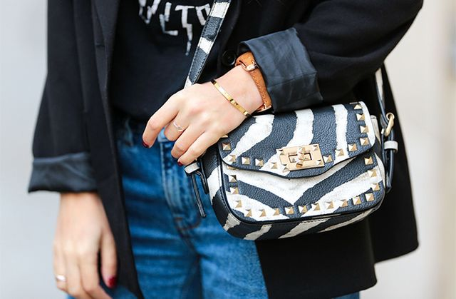 Gold studded zebra crossbody purse on blazer and denim
