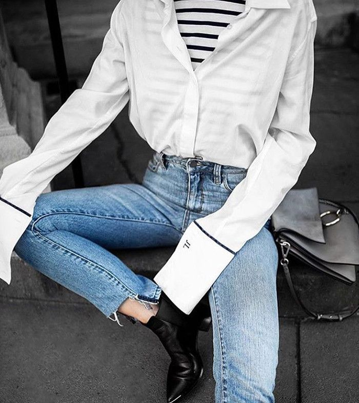Striped tee with high-waisted denim, black ankle boots, and button up blouse with oversized sleeves