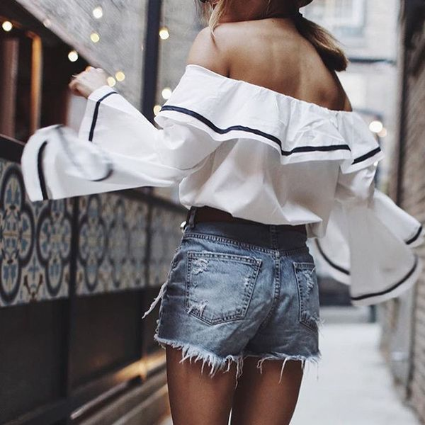 Off-the-shoulder ruffle sleeve white blouse with navy stripes, worn with denim shorts