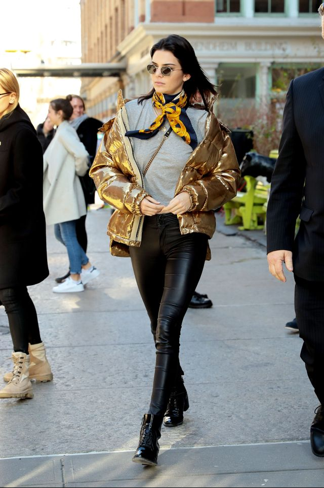Kendall Jenner wearing a puffer jacket, leather pants, and a neckscarf