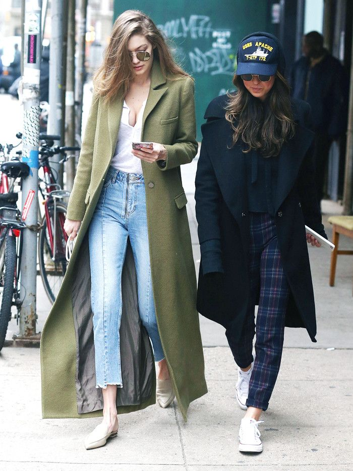 Gigi Hadid wearing a long green coat, skinny jeans, pointed flat ballet pumps, a white jersey top and reflective sunglasses in New York January 2017