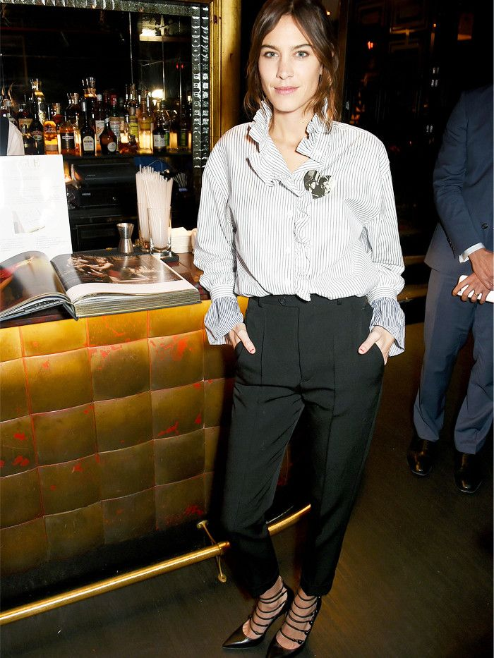 Alexa Chung attends Vogue: Voice of a Century talk in a Burberry striped shirt and black trousers