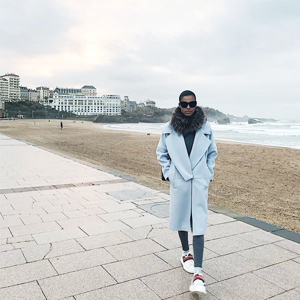 When it's cold back in Biarritz, Kunakey opts for a long pastel coat paired with fur and white sneakers.