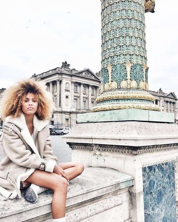 Kunakey takes in the sites of Paris in a shearling coat and white ankle boots.