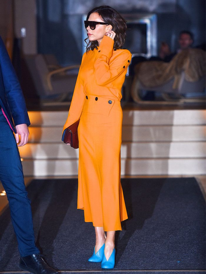 Victoria Beckham wearing orange dress with bright blue shoes