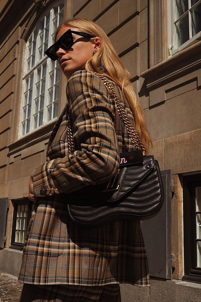 Best checked blazers: Tine Andreaa wearing a brown checked blazer with a black Louis Vuitton bag