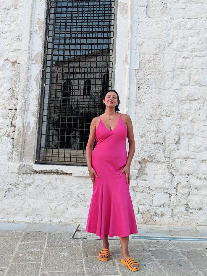 Types of Necklines: Naomi Shimada pairs a V-neck fuchsia dress with orange slides