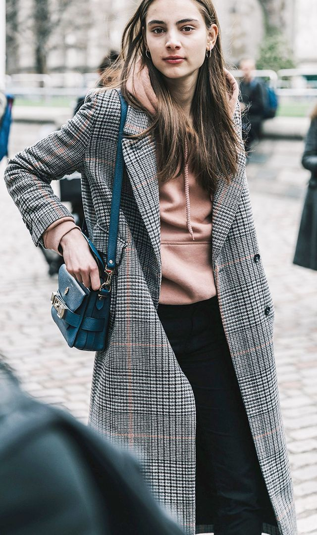 Woman wearing hoodie with coat at London fashion week