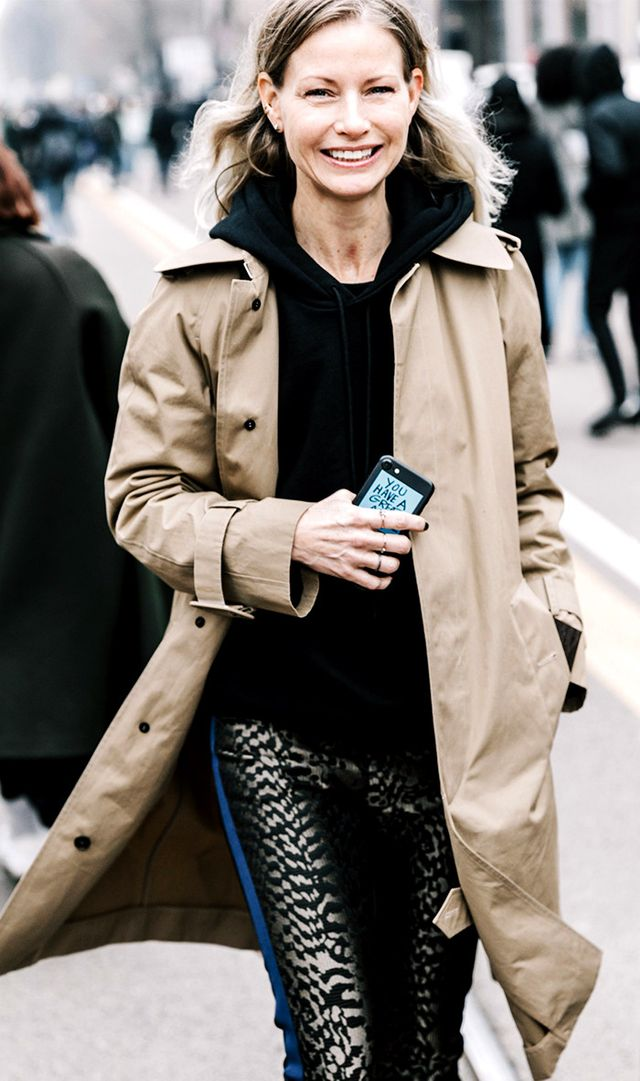 Woman layering a hoodie under a trench coat