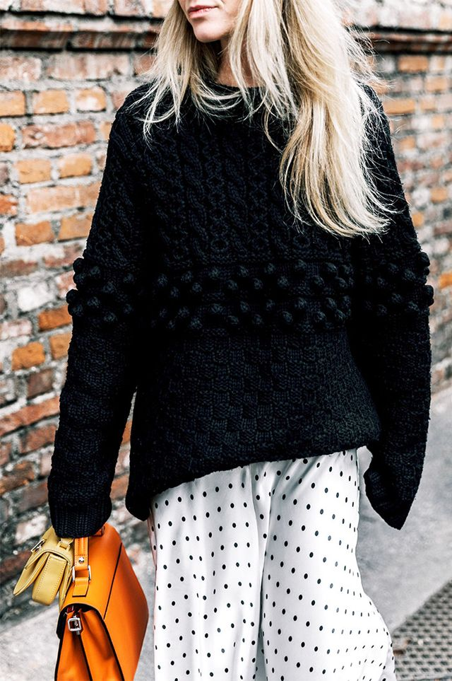 Woman wearing polka dot dress with chunky sweater