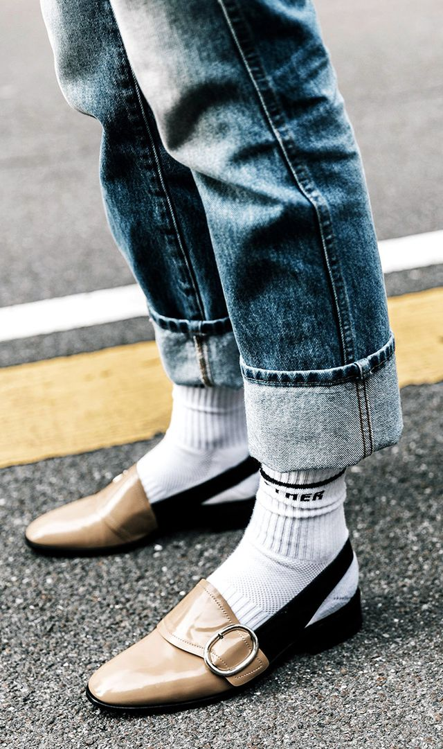 Woman styling her shoes and socks with denim