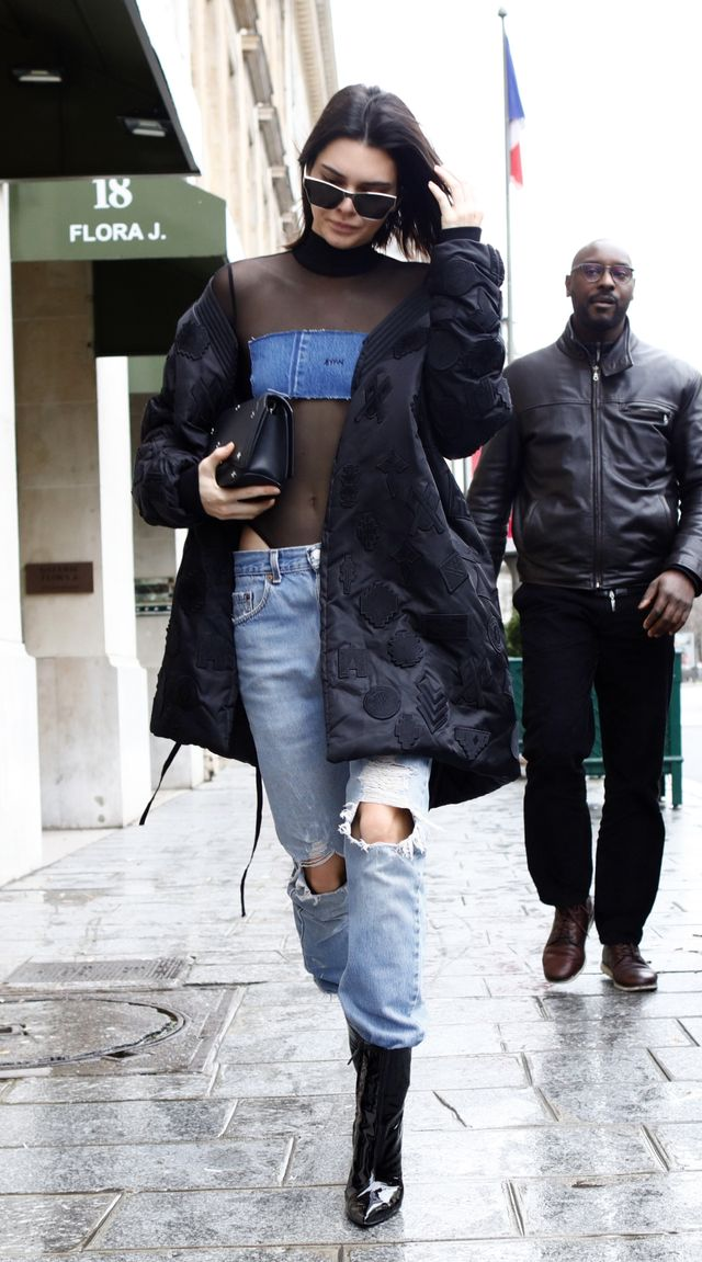 Kendall Jenner wearing a mesh top, jeans and patent black boots